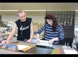 Two students in a lab using screen printing materials