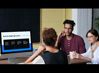 Three people sat around a computer having a discussion